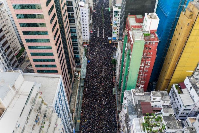 This overhead view shows thousands of protesters marching through the street as they take part in a new rally against a controversial extradition law proposal