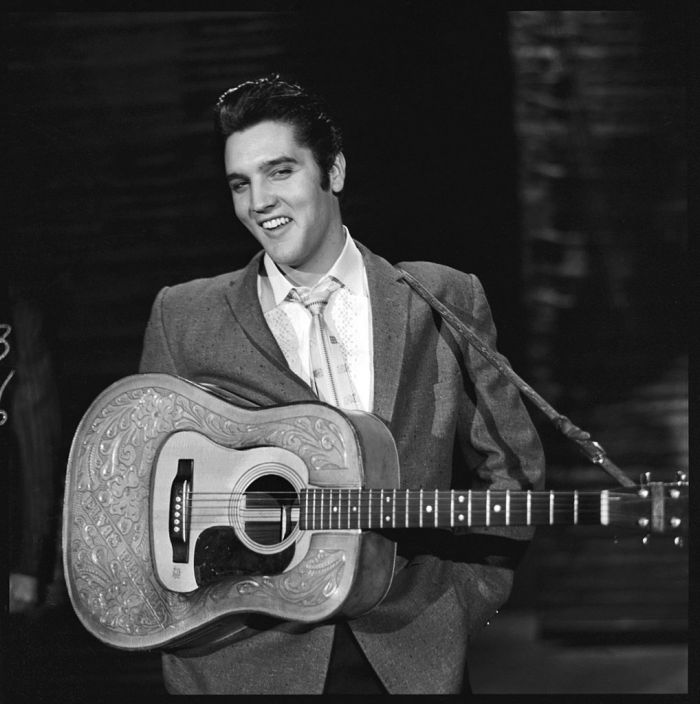 American rock and roll singer and actor Elvis Presley smiles as he stands with his hands in his pockets and a guitar around his shoulders during his second appearance on the Ed Sullivan Show, New York