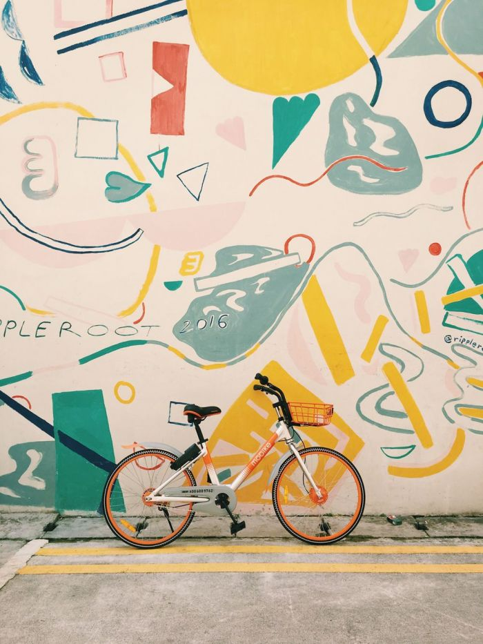 orange and white bicycle leaning on a graffiti wall