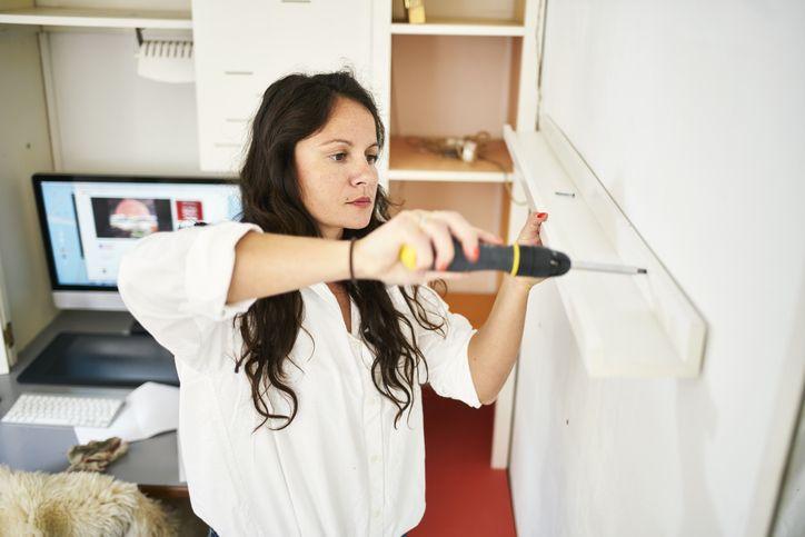 woman installing a shelf