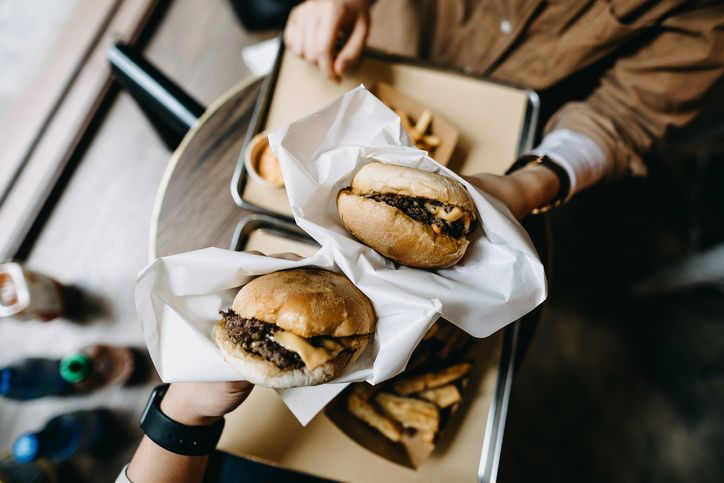 two people holding hamburgers