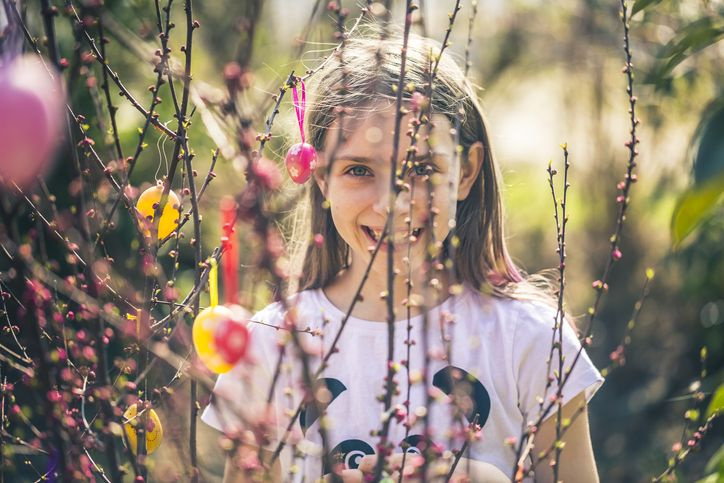 Girl smiling through a bloomingtree