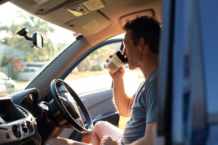 man sipping coffee in his car
