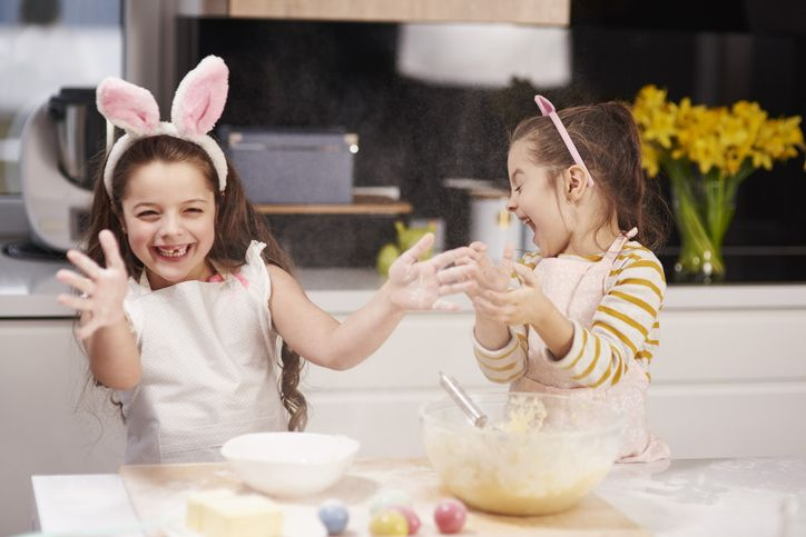 two little girls with bunny ears playing in the kitchen