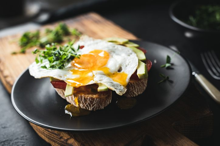 avocado toast served with sunny side up egg