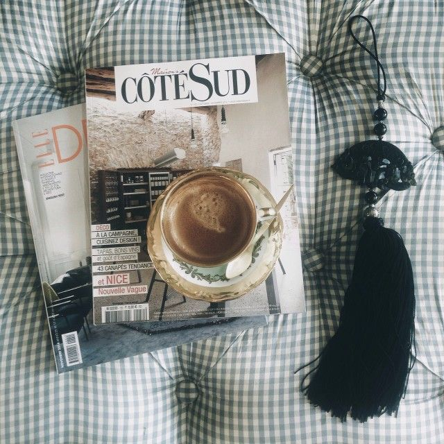 Cup of coffee in a glass mug sitting on top of a stack of exclusive lifestyle magazines