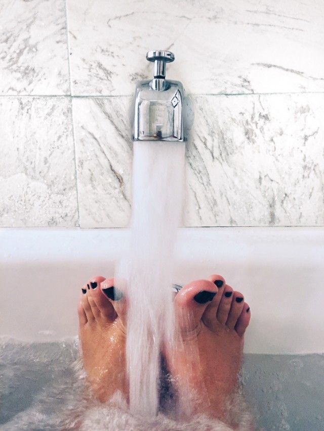 Feet painted with black nail polish resting in bath tub while water is running