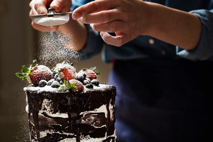 chef sprinkling powder on a cake