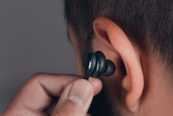 man putting earbud in his ear