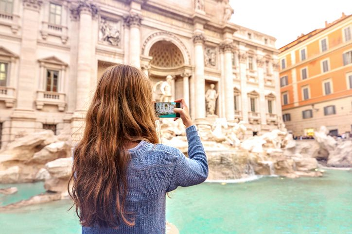girl taking a picture of trevi fountain