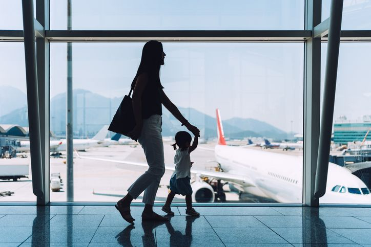 mother and child walking through an airport