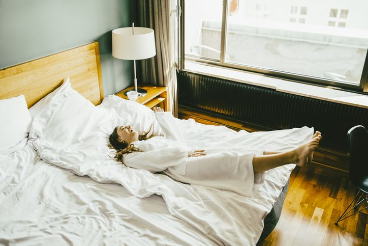 woman lounging on her bed