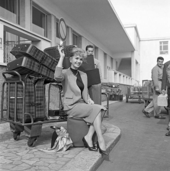 American actress Debbie Reynolds (Mary Frances Reynolds) sitting beside a luggage cart at Ciampino airport. Rome, 23rd March 1959