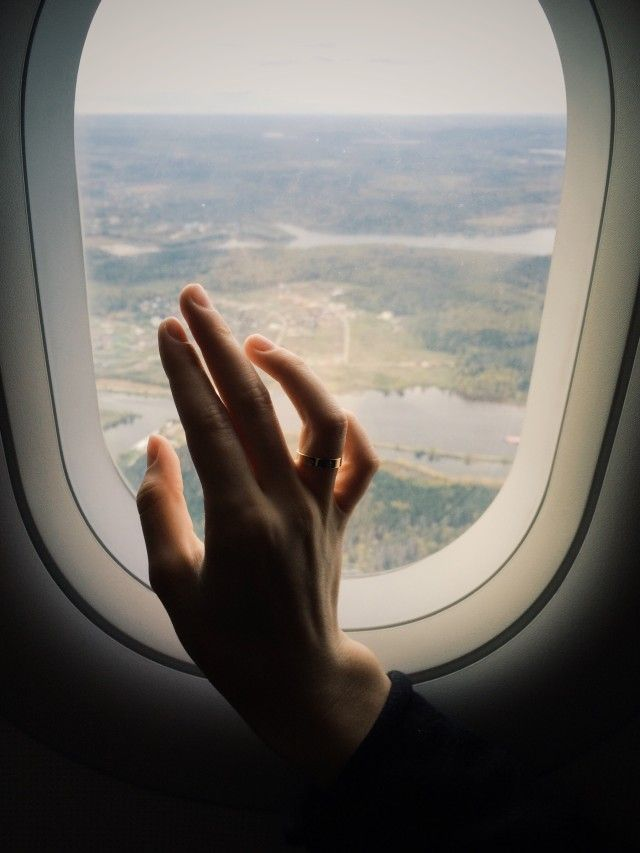 Person resting hand on a window during flight