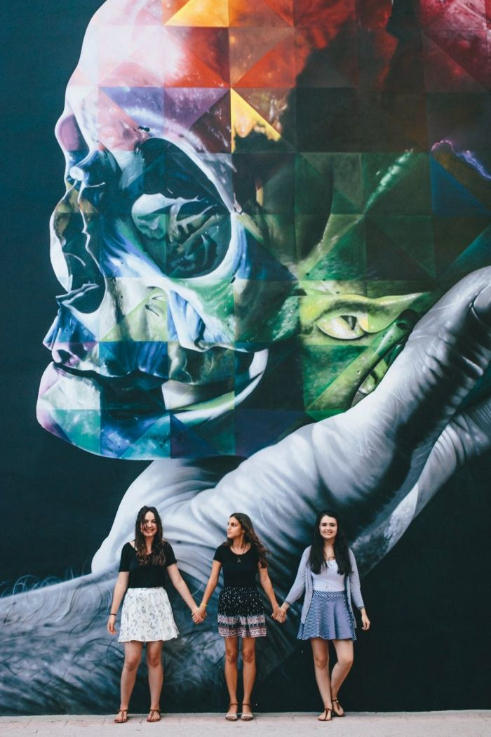A street mural with three girls standing in front