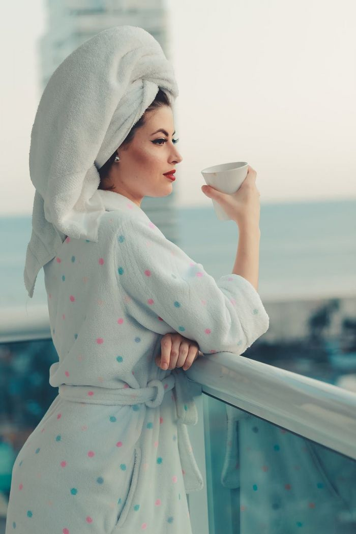 A woman in a bathrobe looking out into the ocean