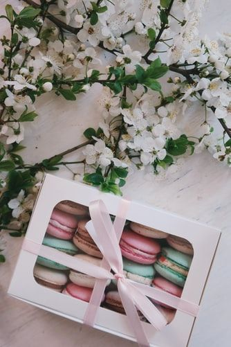 French macarons packaged in a white box and tied with a bow next to white flowers
