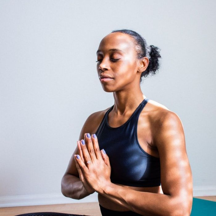 Woman wearing black sports bra and messy bun meditating after yoga class