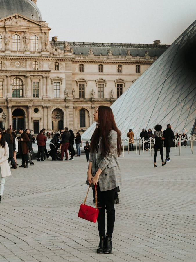 Woman holding her red pocket book standing in front of the Louvre in Paris