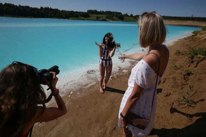 "young woman poses for pictures by a Novosibirsk energy plant's ash dump site - nicknamed the local ""Maldives"""