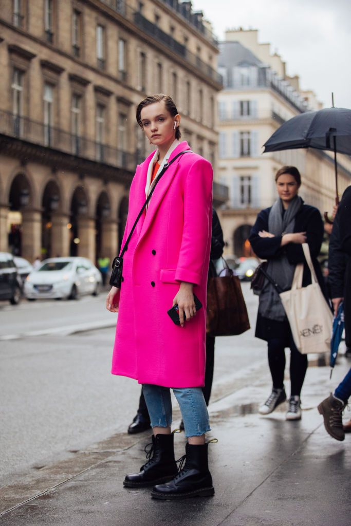 Model Valeria Chenskaya wears Apple Airpods, a hot pink coat, blue jeans, and black Doc Marten boots after the Giambattista Valli show