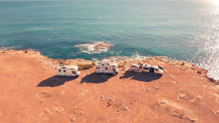 Three RV's parked on the edge of a cliff overlooking the ocean in Toerrevieja, Spain