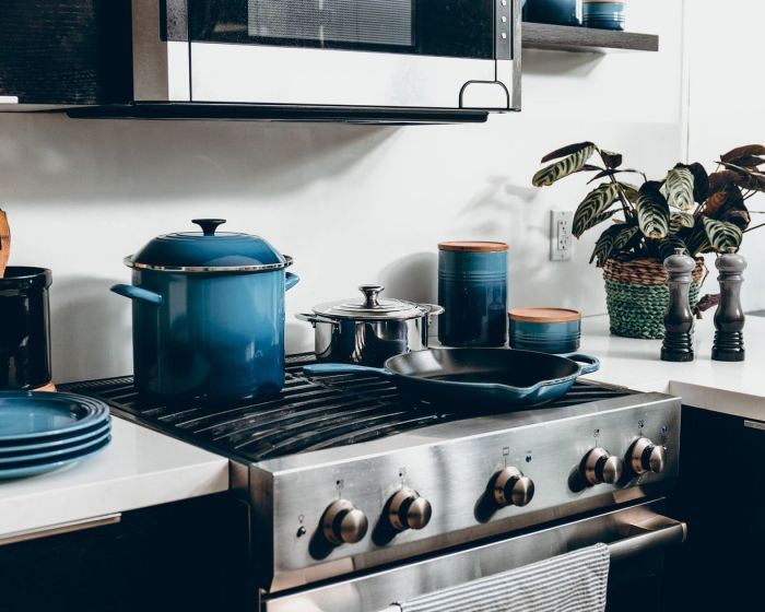 Blue ceramic pots and pans on a stove top in a brand new modern kitchen