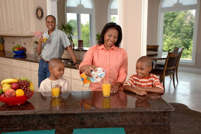 An African-American family (adult male and female and two male children) are drinking juice in a kitchen