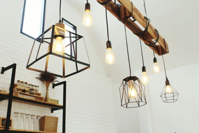 Low angle view of pendant light hanging from ceiling against white brick wall
