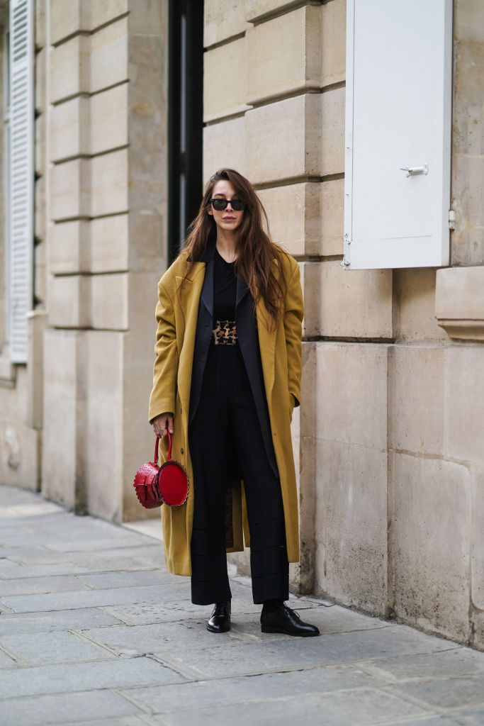 Stylist Estelle Chemouny wears a long beige overcoat and black shirt and pants at Paris Fashion Week