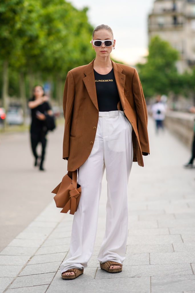 Woman wearing white pants and brown oversized blazer on the street