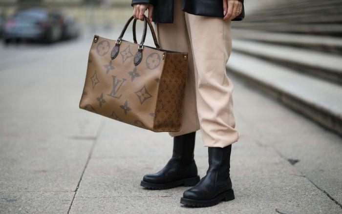 Woman in beige pants holding an oversized Louis Vuitton handbag