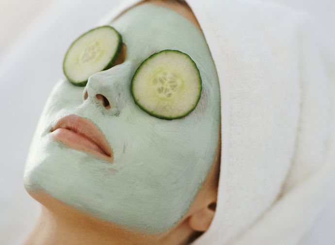 Woman with facial mask, towel wrapped around her hair, and cucumber slices on her eyes