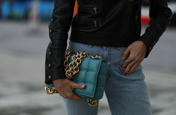 Close-up of woman wearing light jeans and black leather jacket holding a Bottega Veneta bag