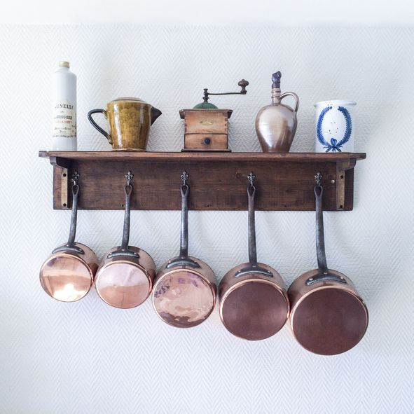 Saucepans And Utensils Hanging From Hooks Below Shelf On Wall In Kitchen