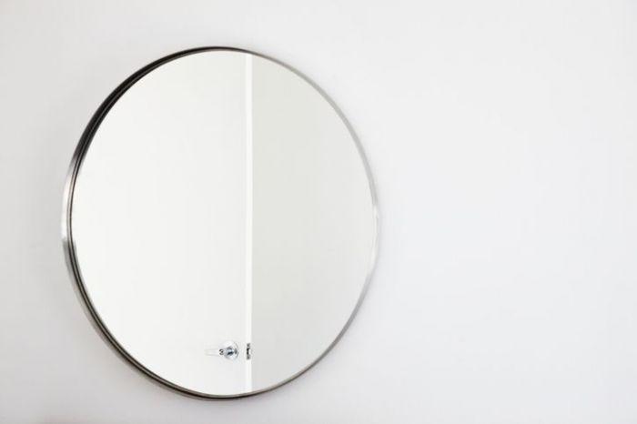 Round mirror on a white wall